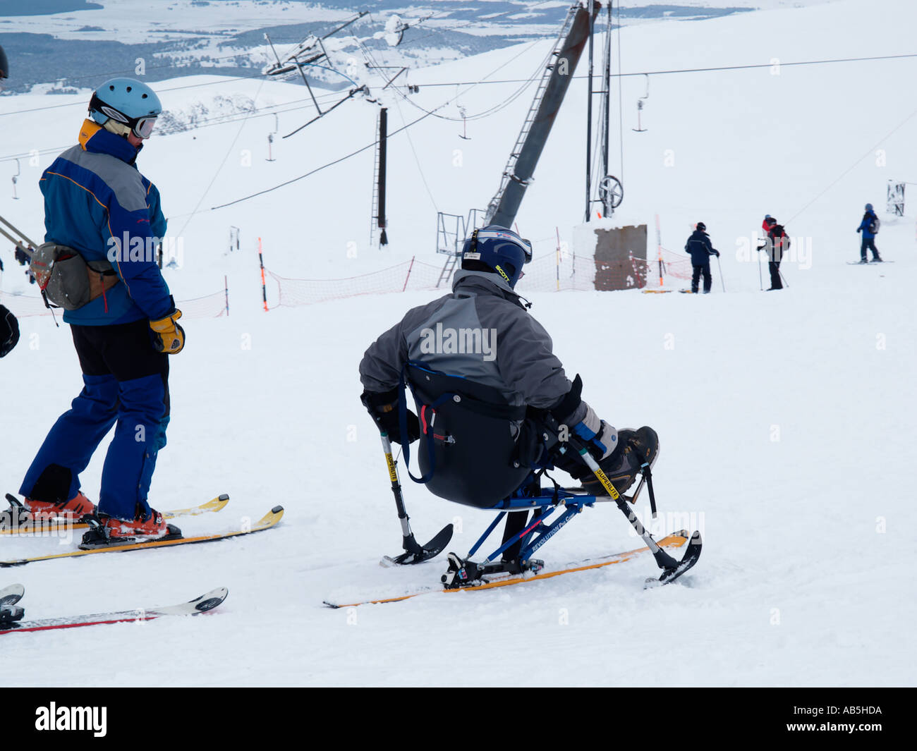 DISABLED SKIER sat on a MONO SKI on Cairngorm mountain ski centre with able bodied skiers Cairn Gorm Highland Scotland UK - Stock Image
