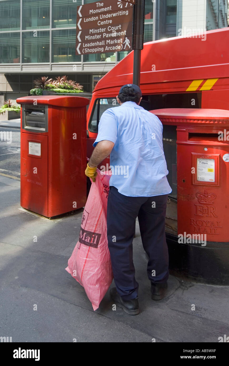 City of London postman emptying mail box - Stock Image