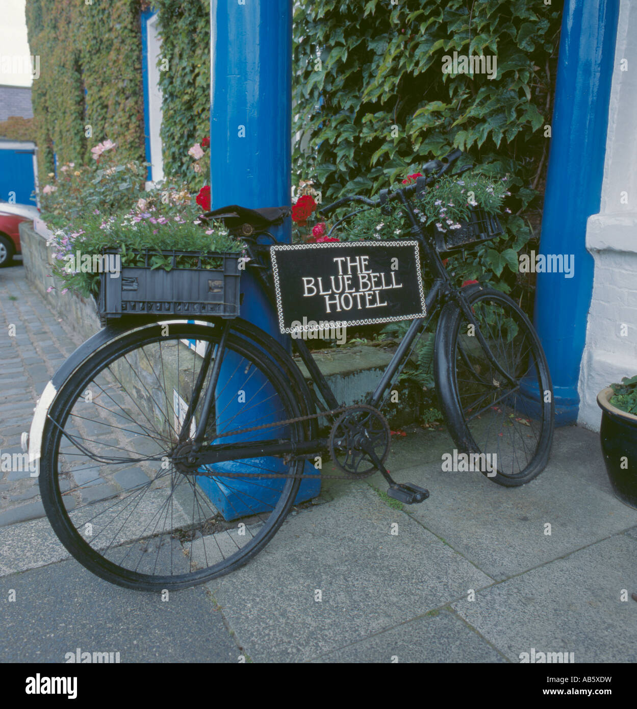 Old bicycle with sign and flower box milk bottle crates, Blue Bell Hotel, Belford, Northumberland, England, UK. - Stock Image