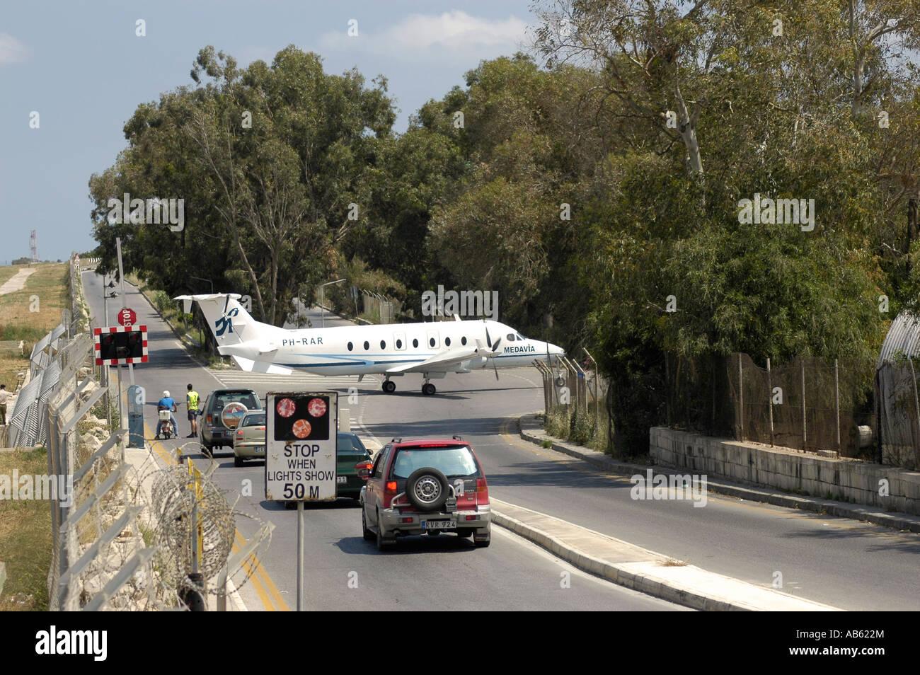 Aeroplane crossing the road. Beech 1900D Medical Evacuation  Plane - Stock Image