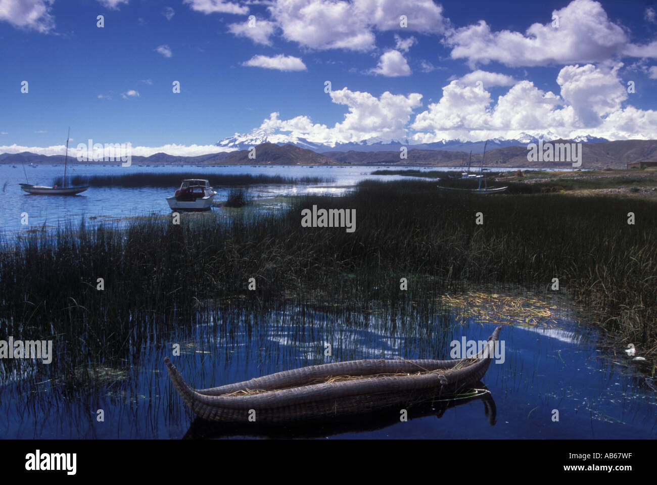 traditional reed boat and modern motorbots anchored at Lake Titicaca with Cordillera real in back Altiplano Bolivia - Stock Image