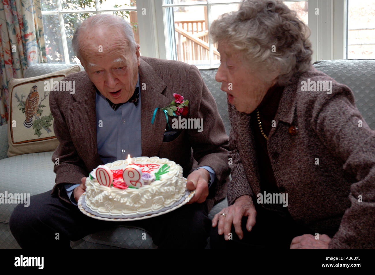 Wife Helping Ninety Year Old Man Blow Out Candles On Cake At His 90th Birthday Party