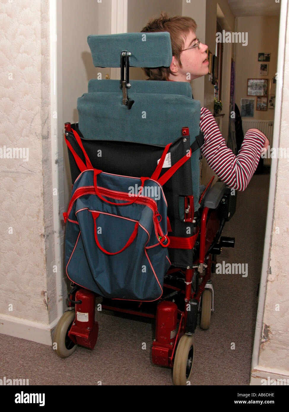 18yr old teenage girl with cerebral palsy managing to manoeuvre wheelchair to get down corridor - Stock Image