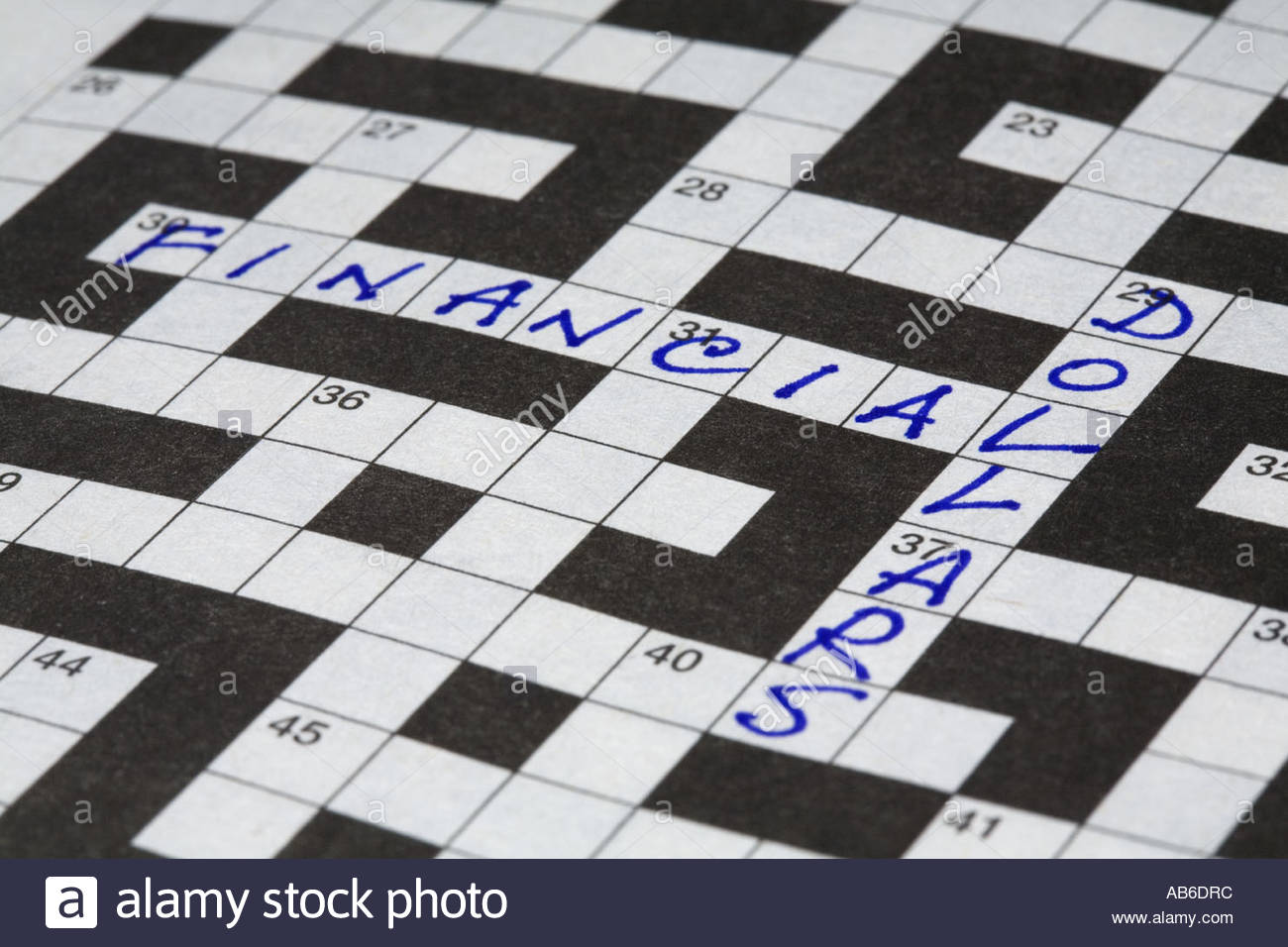 Close up of the words financial and dollars filled in on a  crossword puzzle. - Stock Image