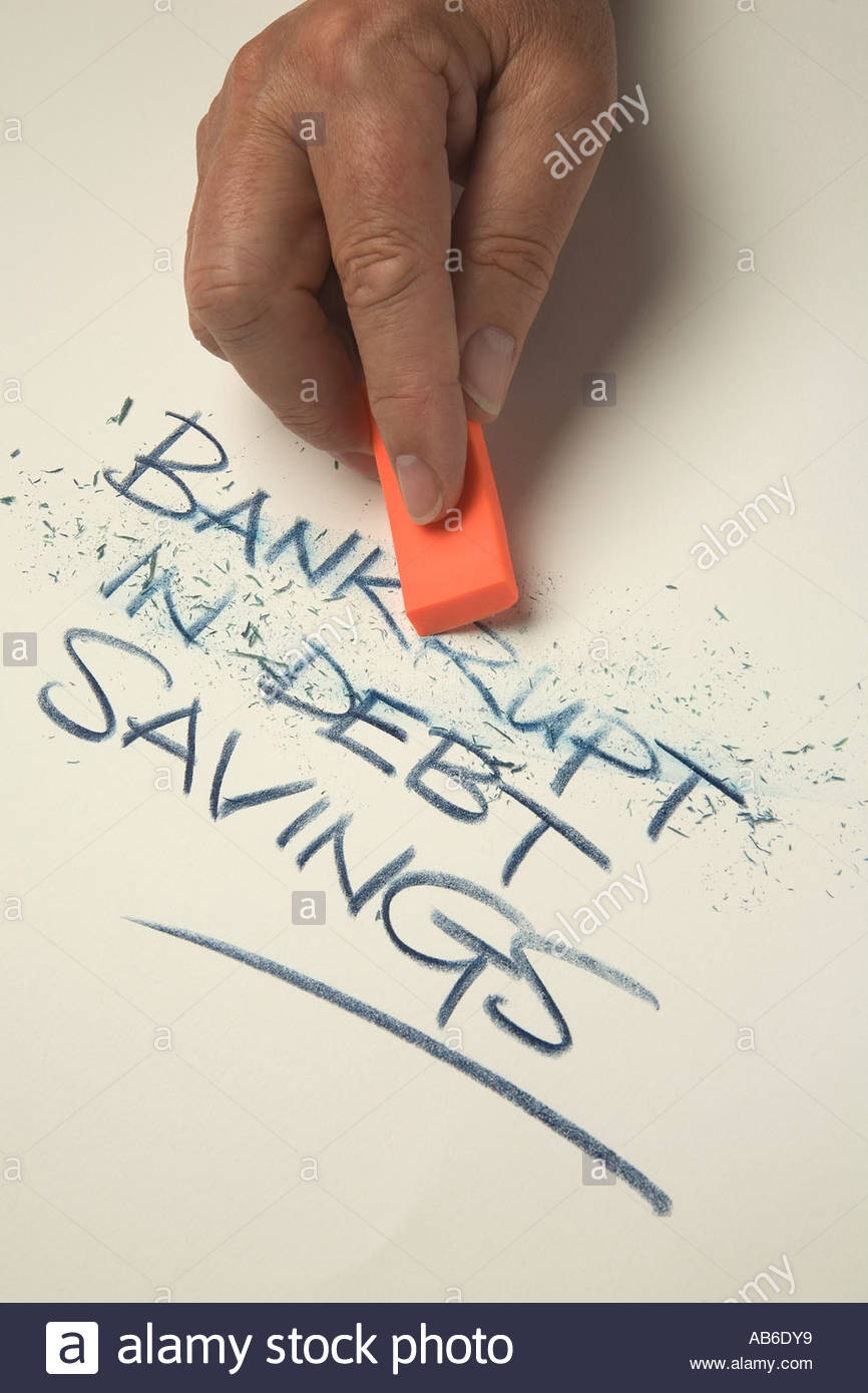 Mans hand holding an orange eraser and rubbing out the words bankrupt, in debt, and  leaving the word savings. - Stock Image