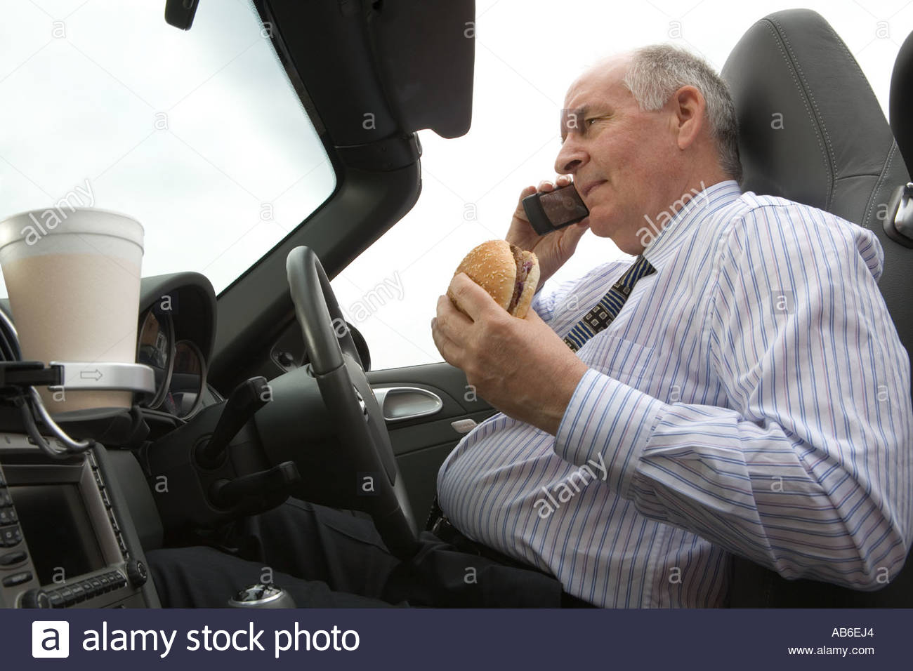 Overweight senior businessman talking on a mobile phone and having a junk food snack in his car - Stock Image