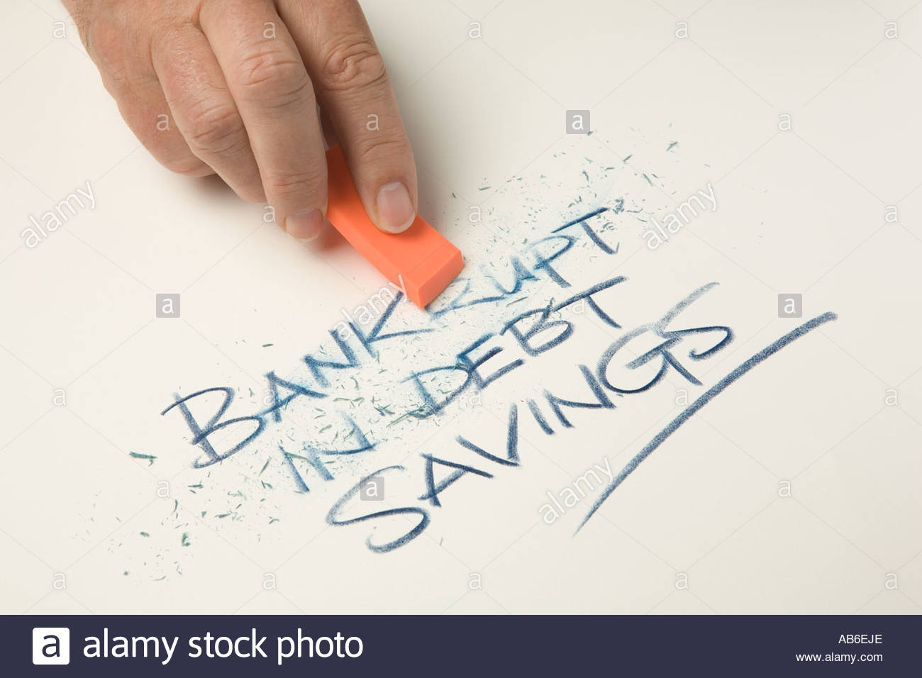 Mans hand holding a orange eraser rubbing out the words bankrupt and in debt. - Stock Image