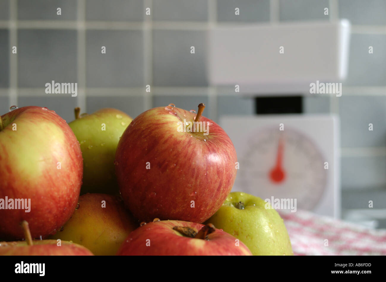 A PILE OF APPLES WITH A SET OF KITCHEN SCALES IN BACKGROUND - Stock Image