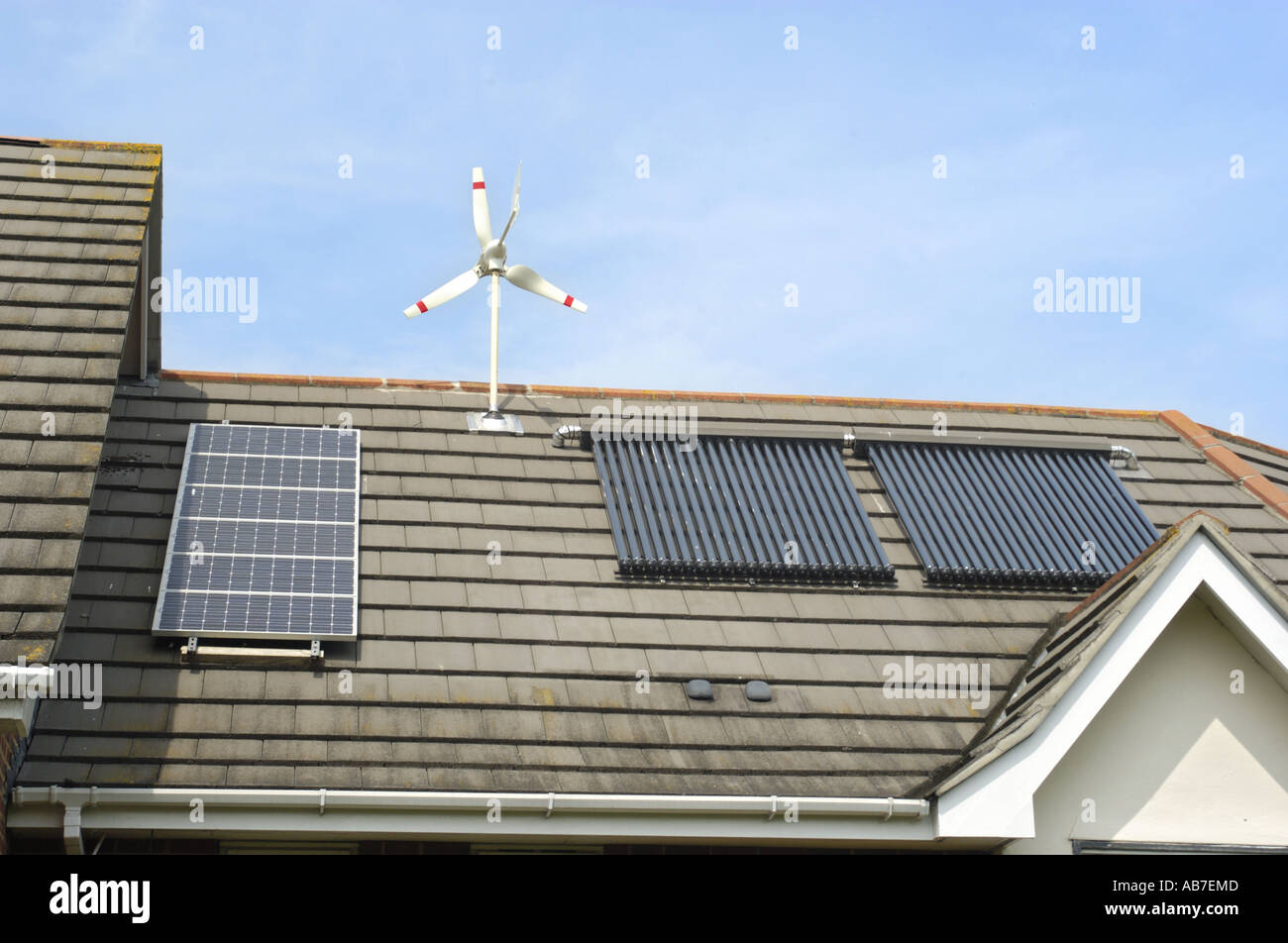 Micro Wind Turbinen  evacuated tube and photo voltaics cells on house in Ferndown Dorset England supplied by Powertech Solar Ltd - Stock Image
