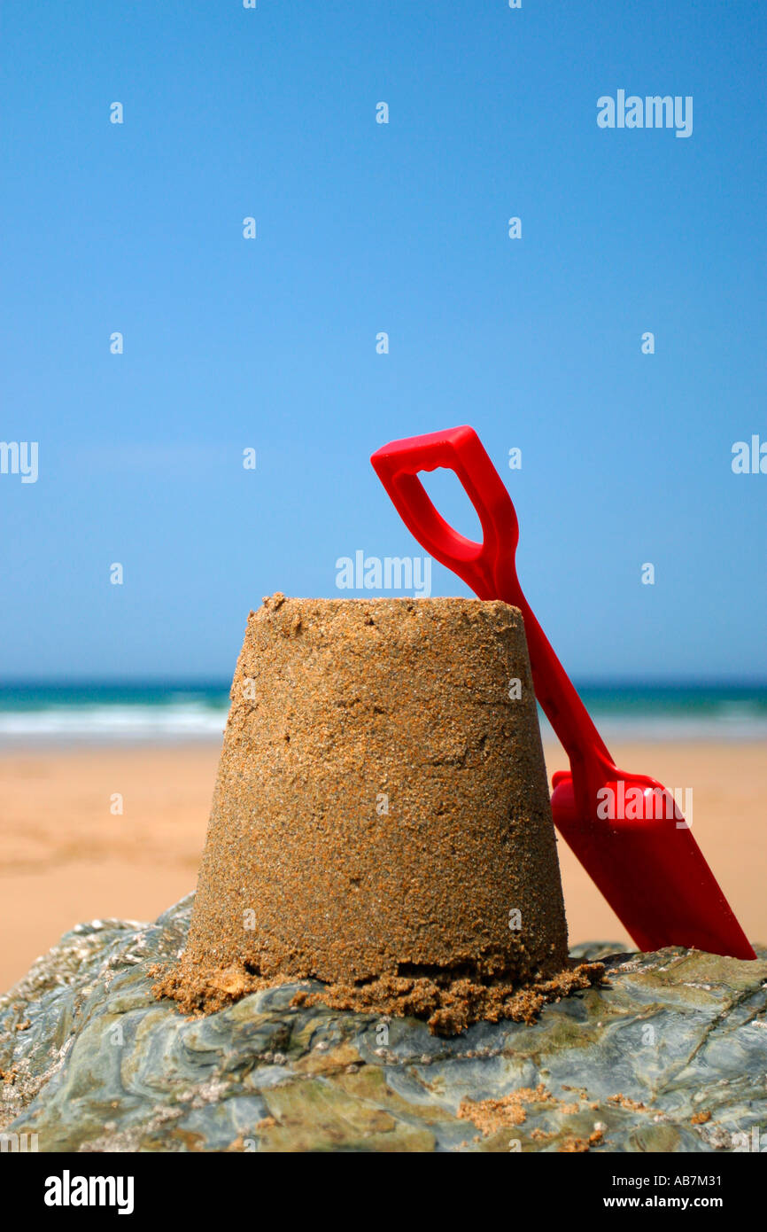 Sandcastle and red spade on rock. - Stock Image