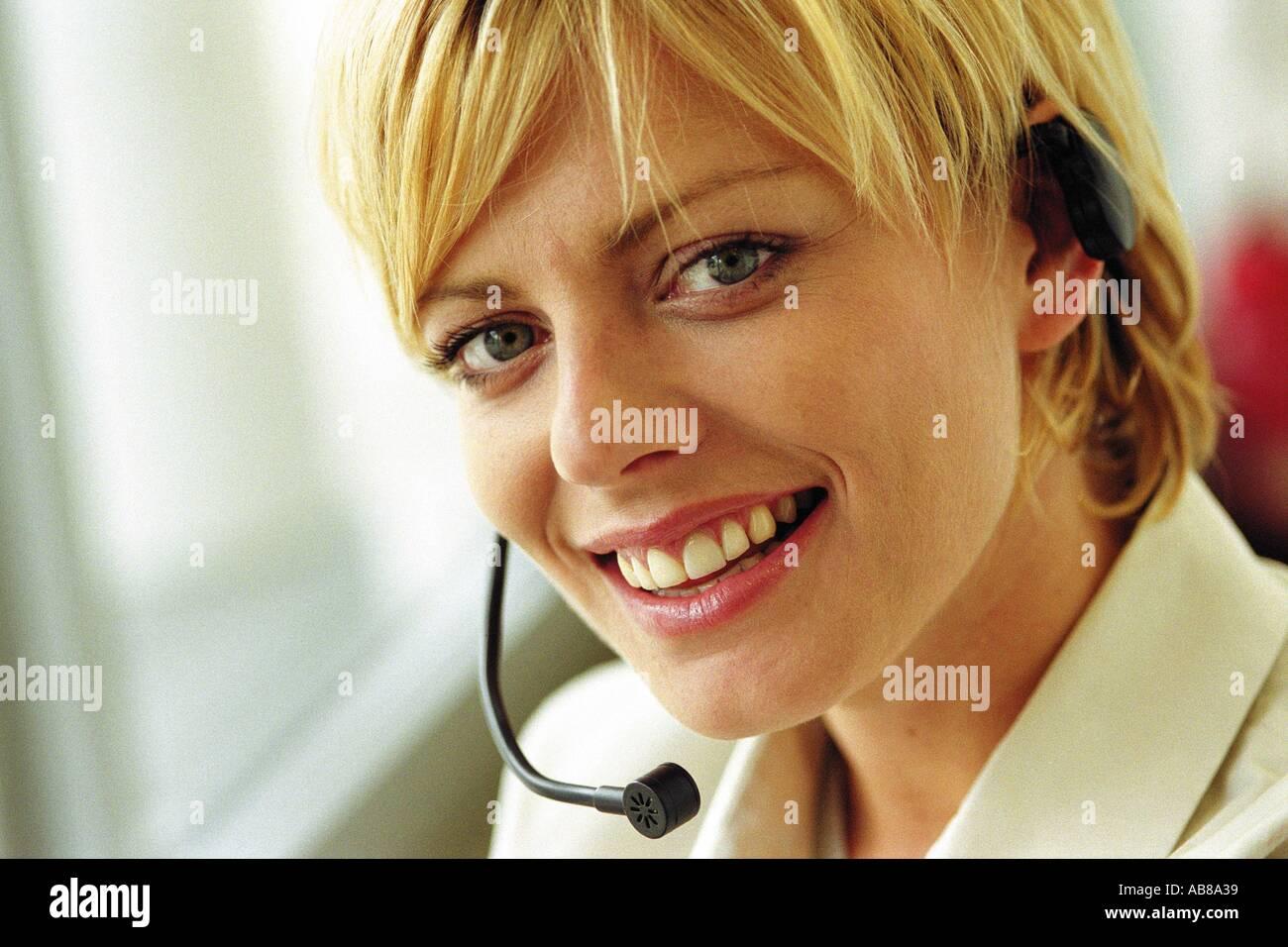 Woman wearing a telephon headset - Stock Image