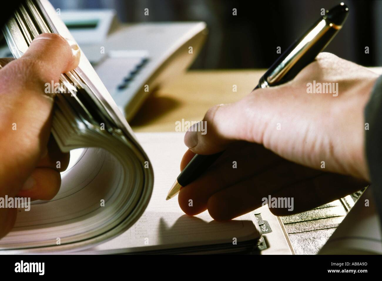 Person writing in address book - Stock Image