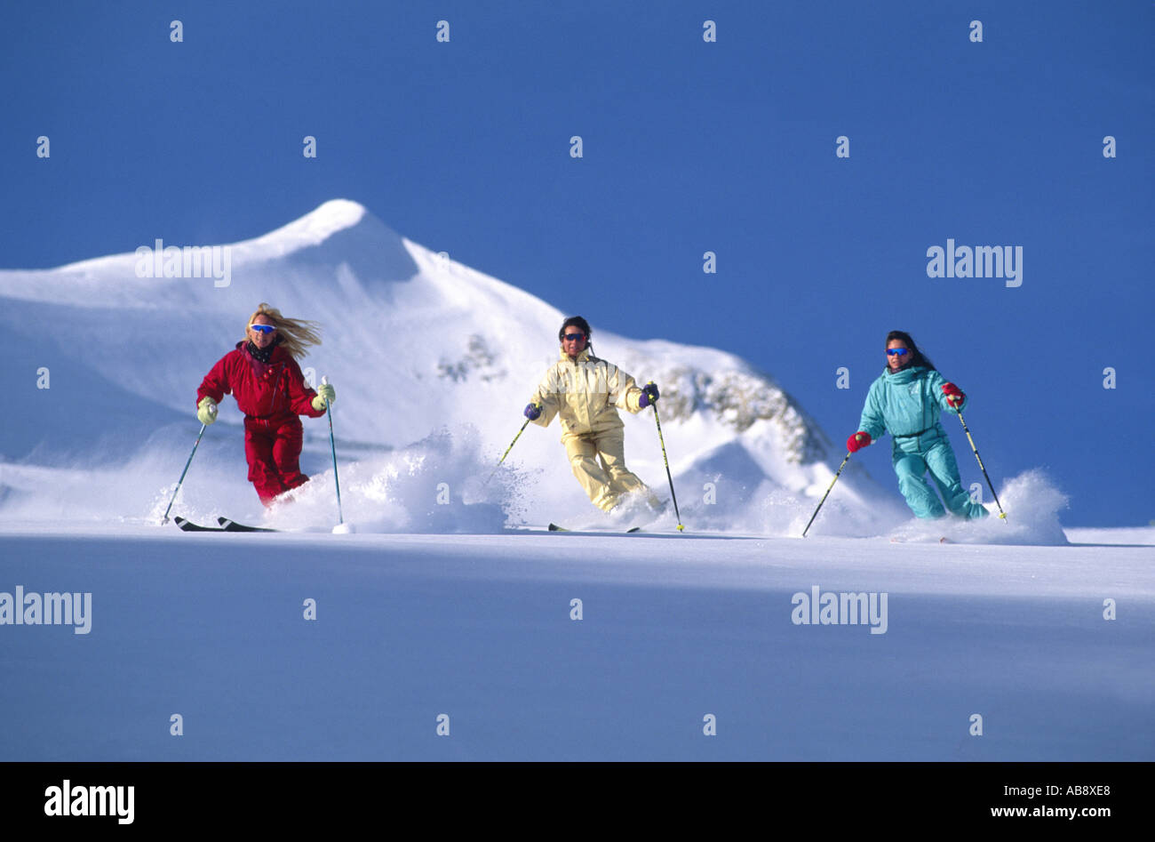 three young women running down a ski piste, side by side, contrasting colours of snowsuits, France, Rhne-Alpes. - Stock Image
