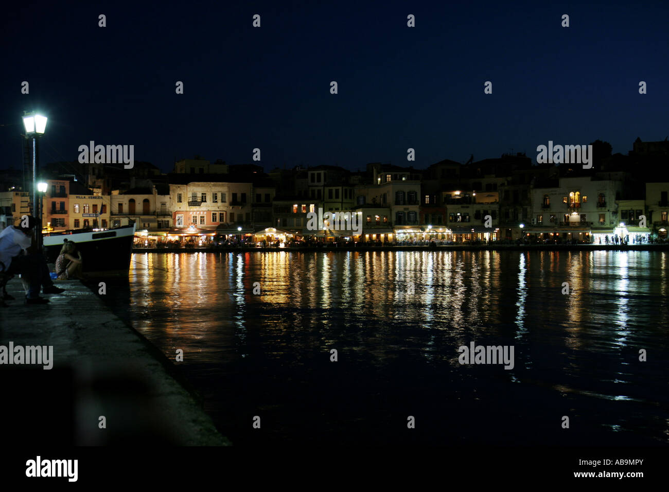 Restaurants and shops after sunset at the old Venetian harbour in Chania, Crete, Greece - Stock Image