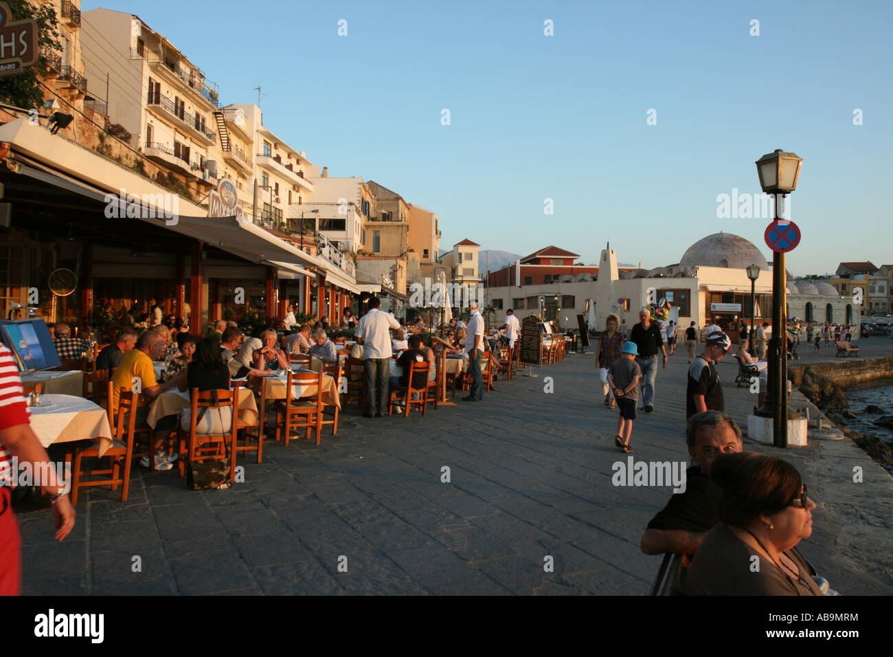 Tourists at restaurants at the old Venetian harbour at sunset in Chania, Crete, Greece - Stock Image