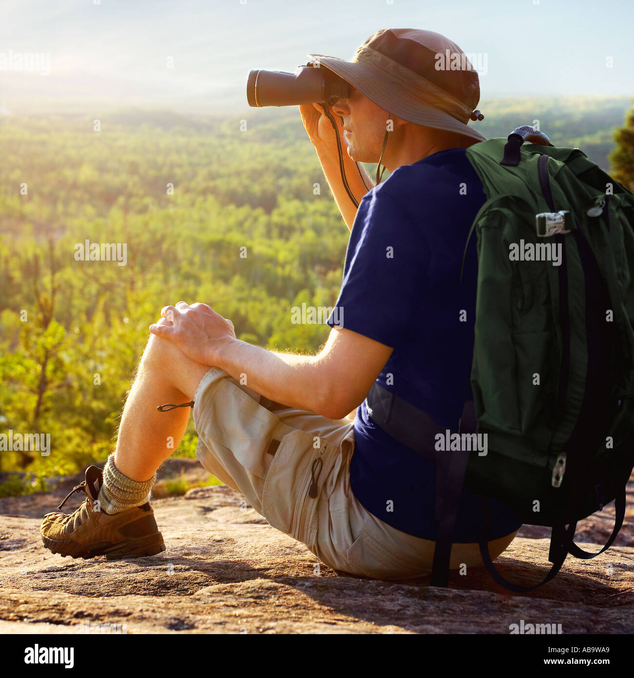 Male hiker with backpack sitting on a hillside looking through binoculars at wilderness - Stock Image