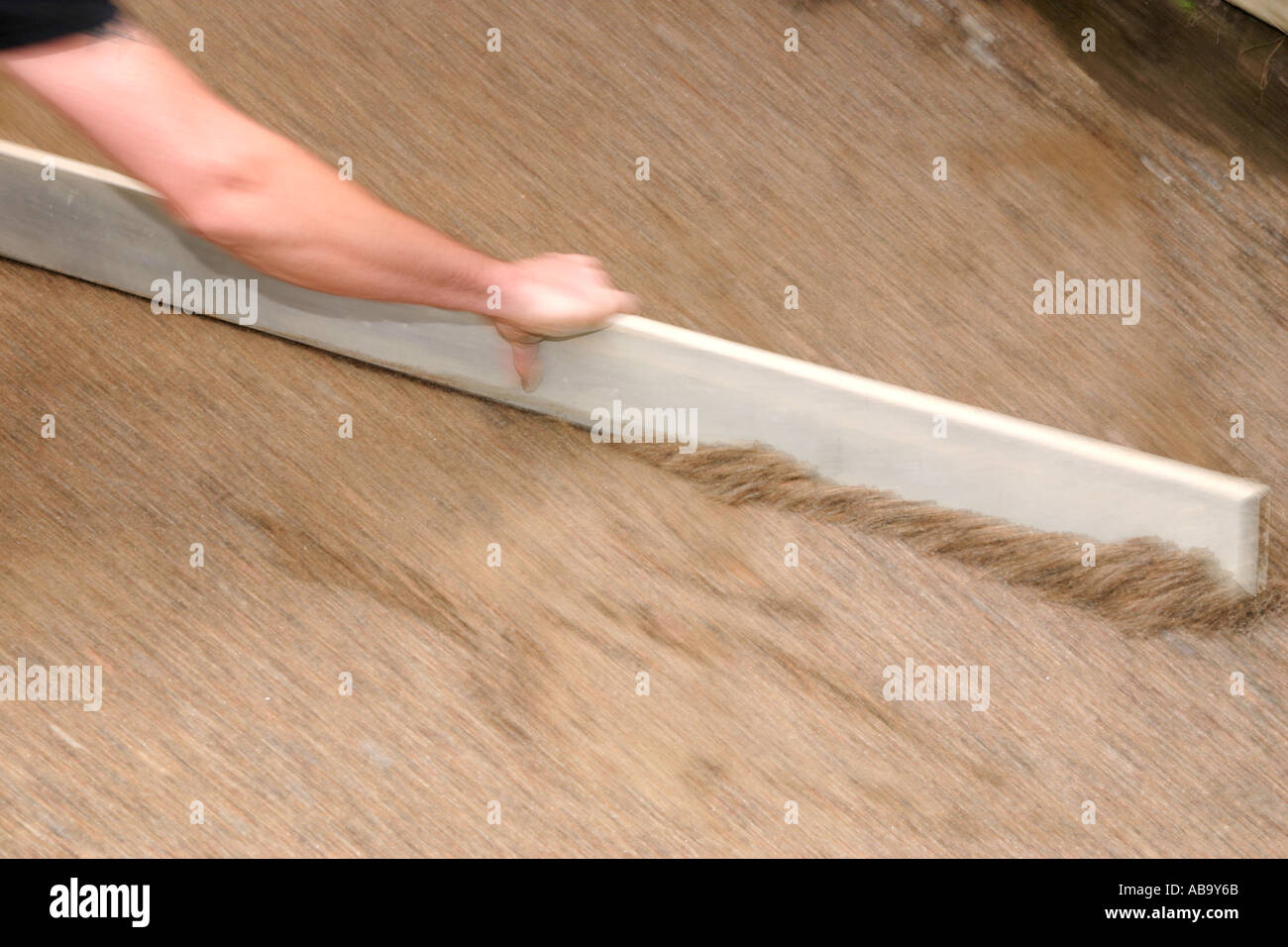 Leveling out sand with a metal plank Stock Photo