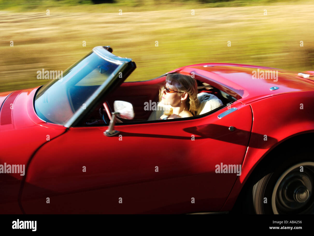 Blond Girl Driving Red Convertible Corvette Stock Photo