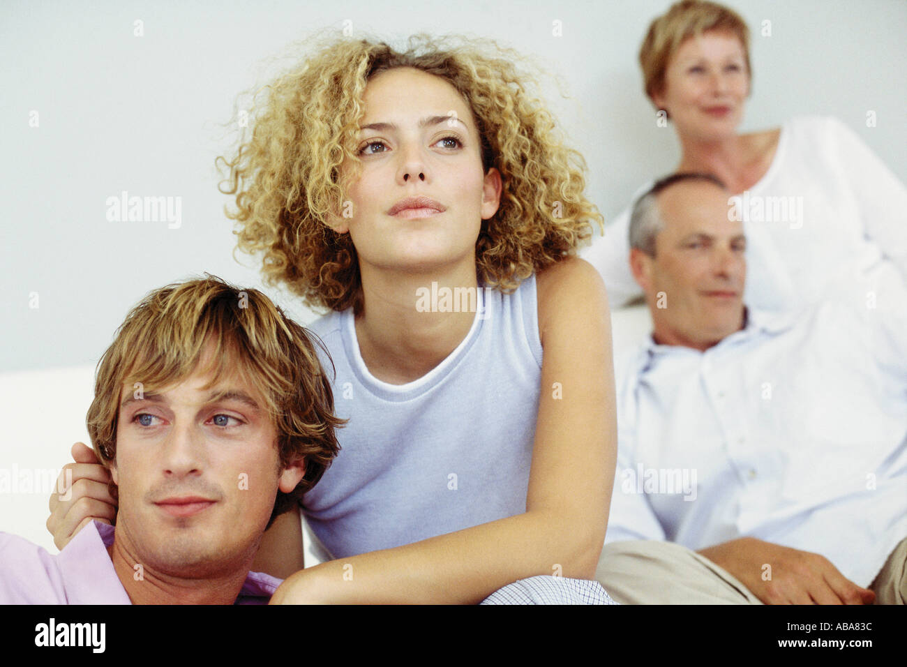 Young couple with in-laws in the background - Stock Image