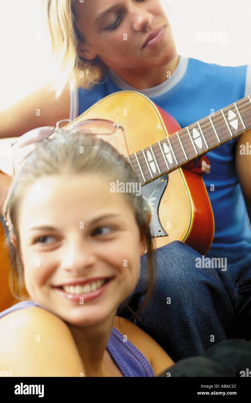 Teenage boy and girl playing the guitar - Stock Image