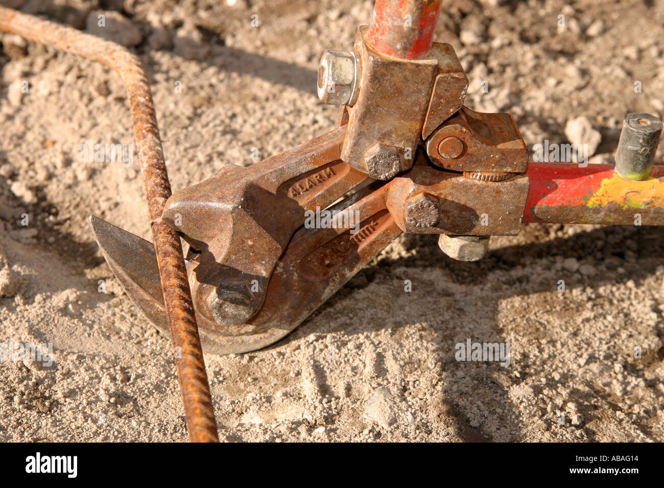 Using a cutting pliers on an iron reinforcement bar - Stock Image
