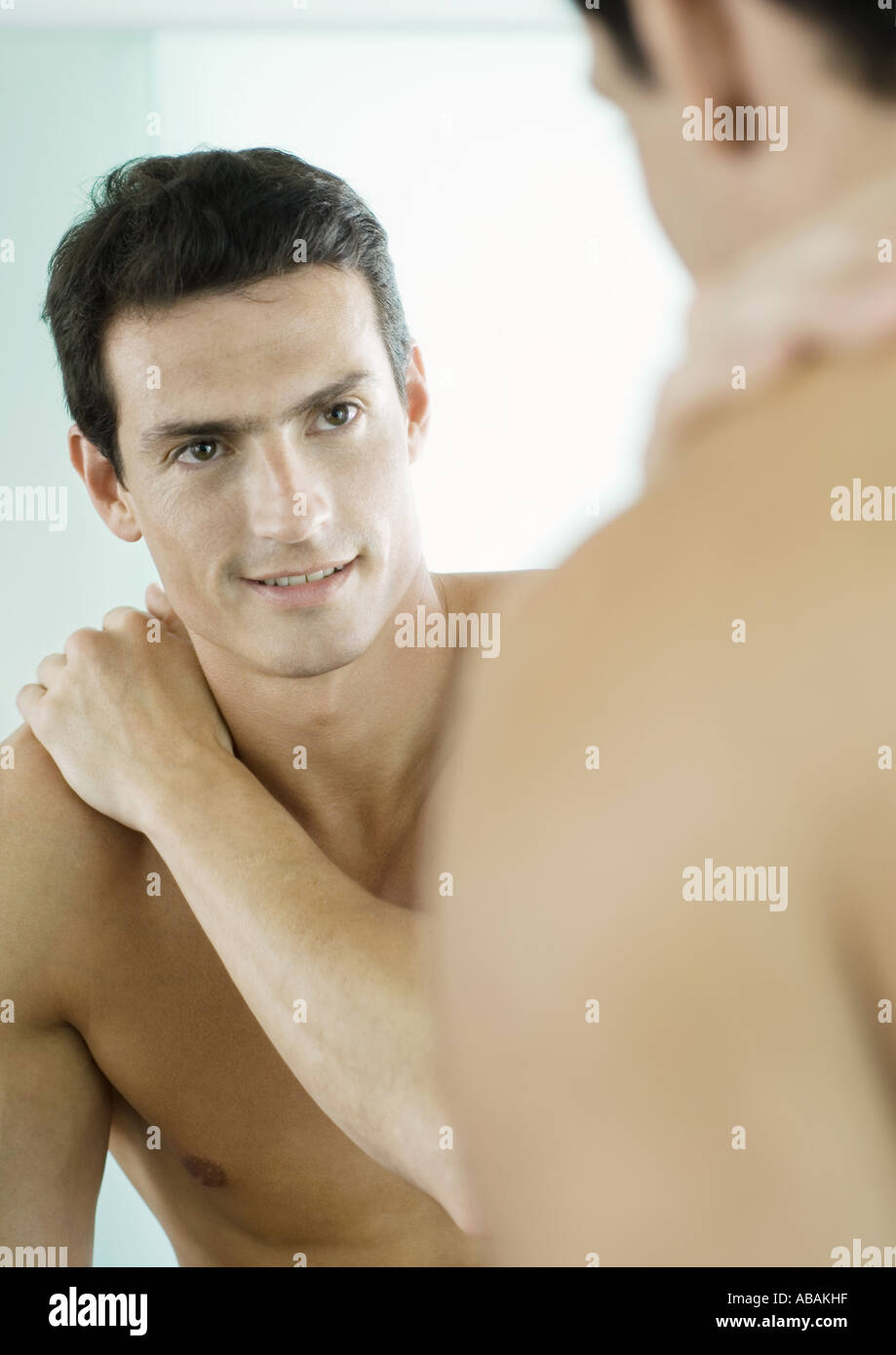 Barechested man smiling at self in mirror - Stock Image