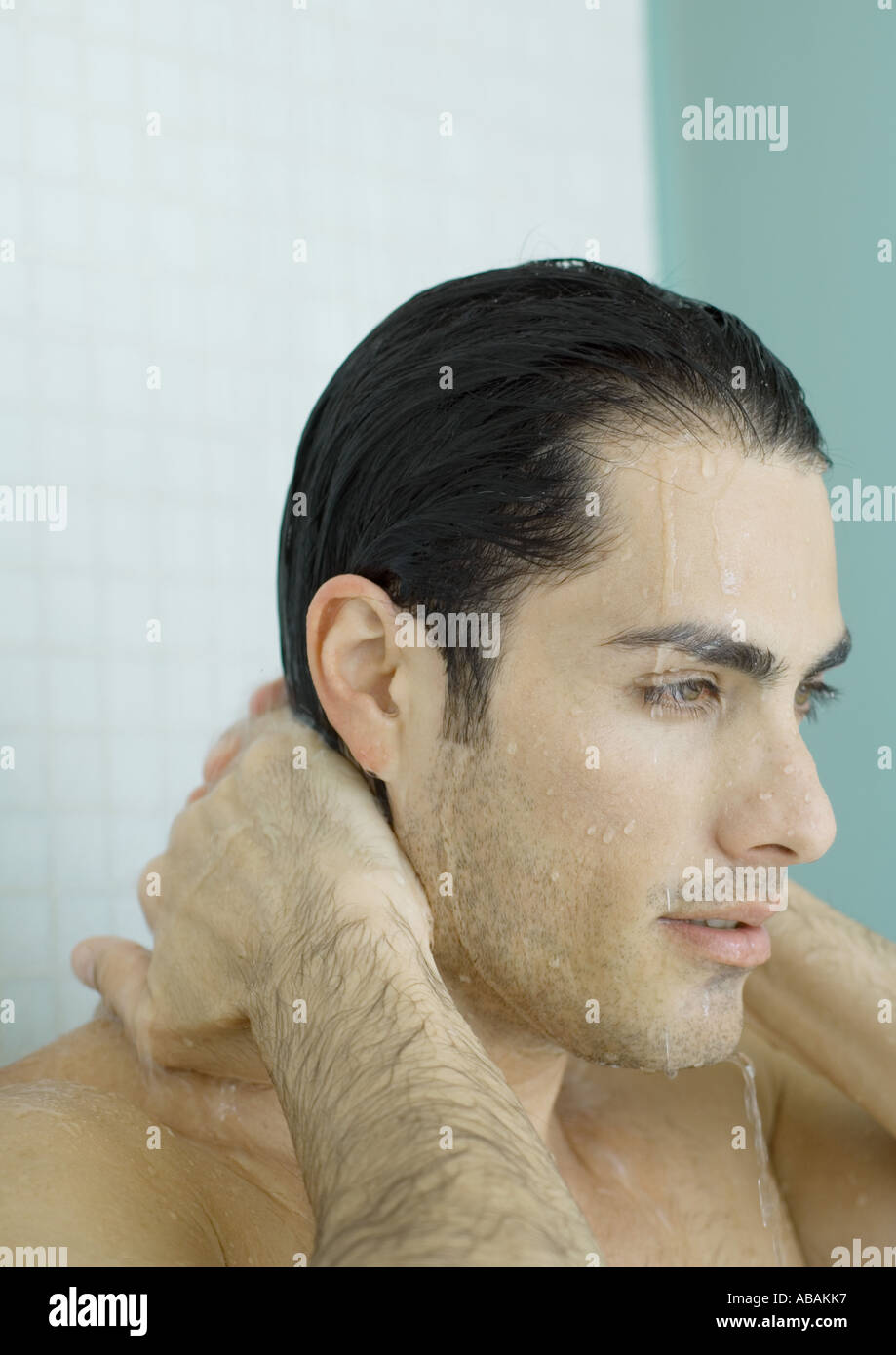 Man with hands behind neck in shower - Stock Image