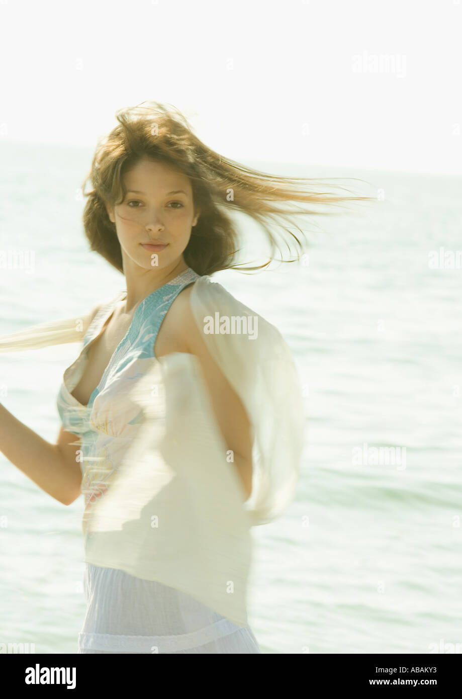 Woman standing in front of ocean in wind - Stock Image