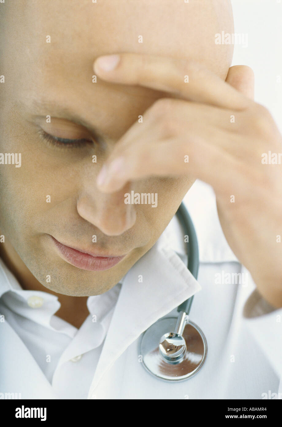 Doctor holding head and looking down - Stock Image