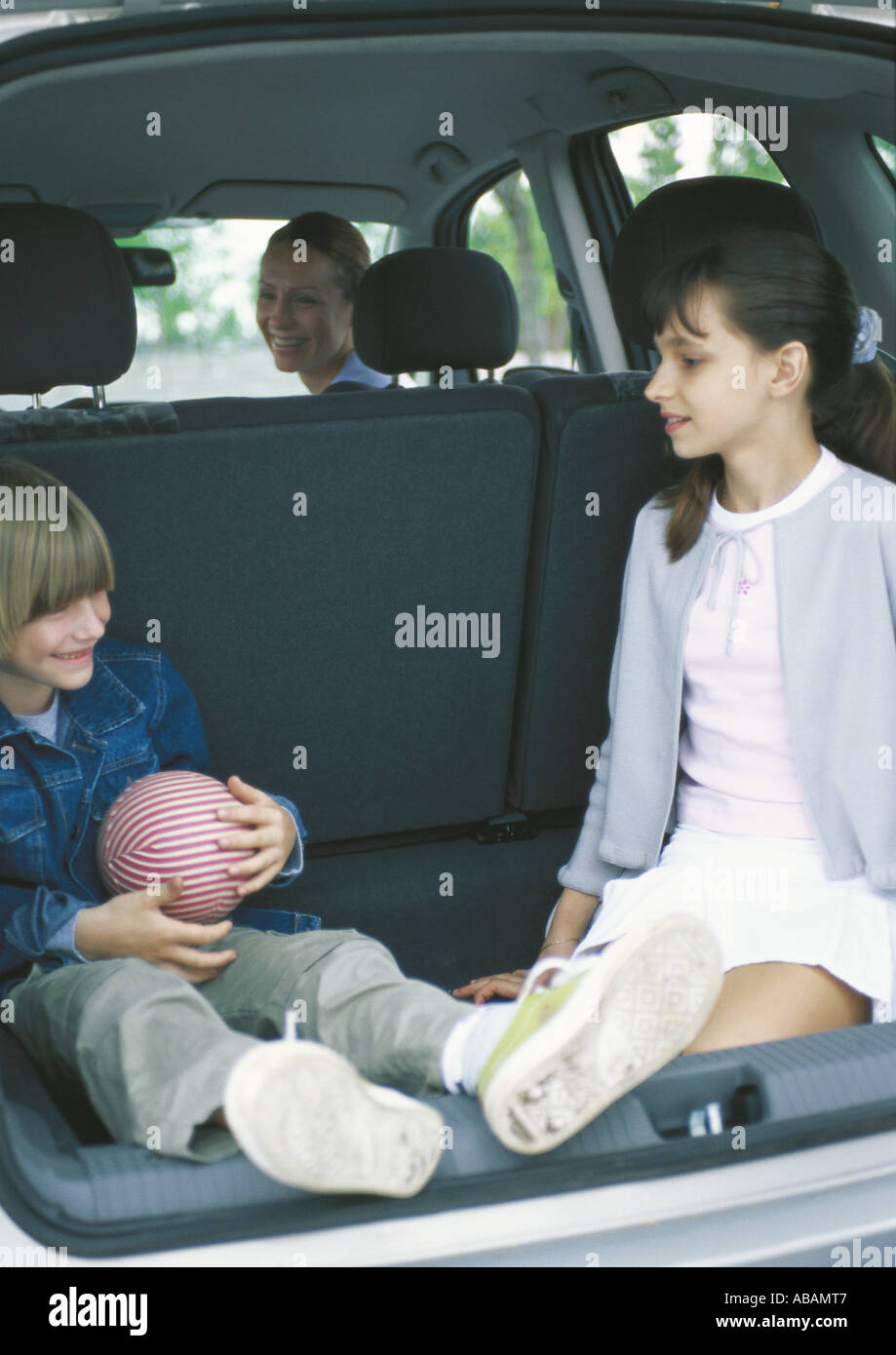 Children sitting in car trunk - Stock Image
