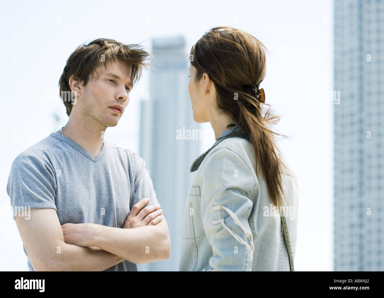 Young couple having argument in front of highrises Stock Photo