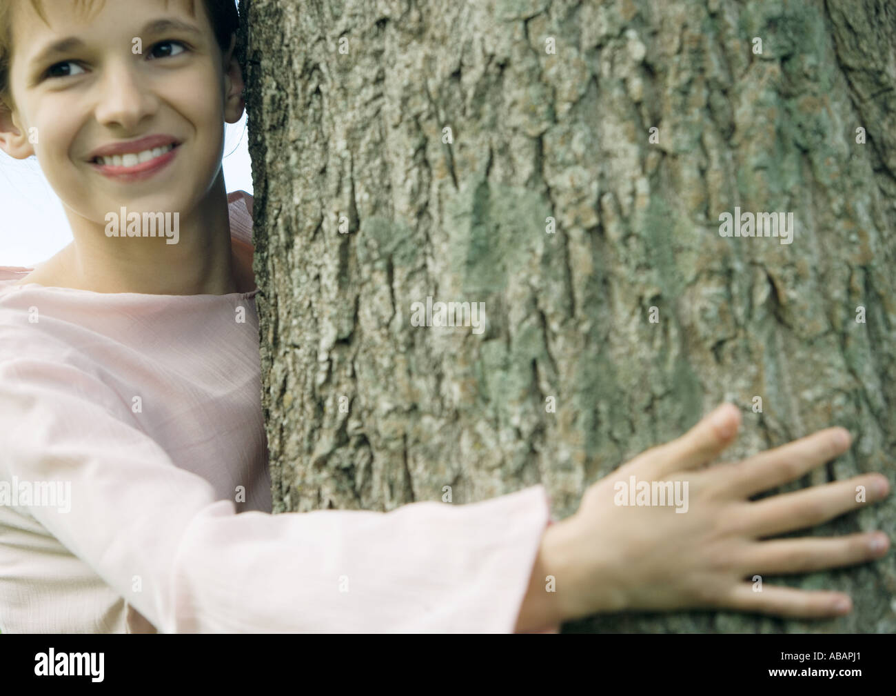 Girl with arm around tree, smiling - Stock Image