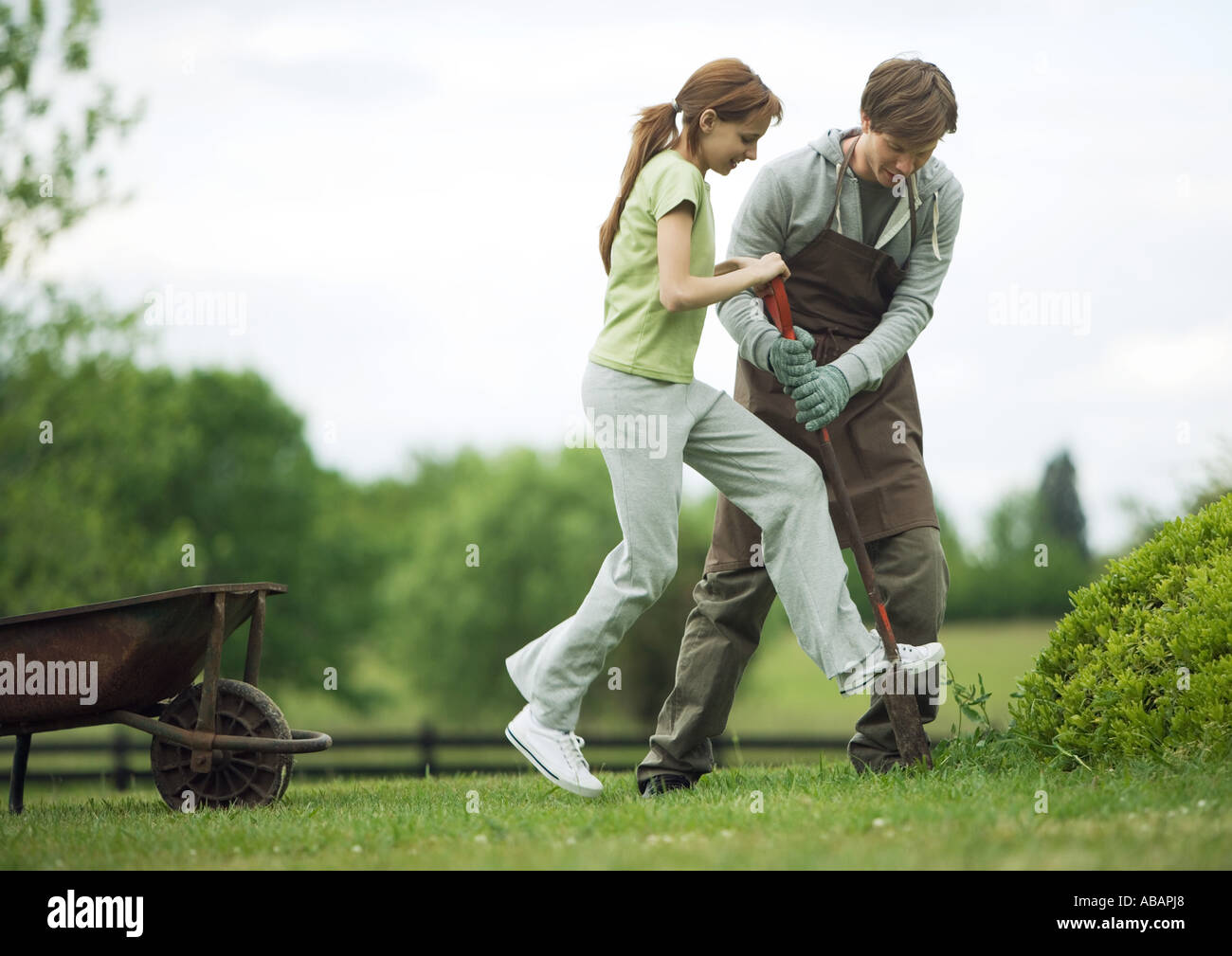 Man helping girl dig in yard - Stock Image
