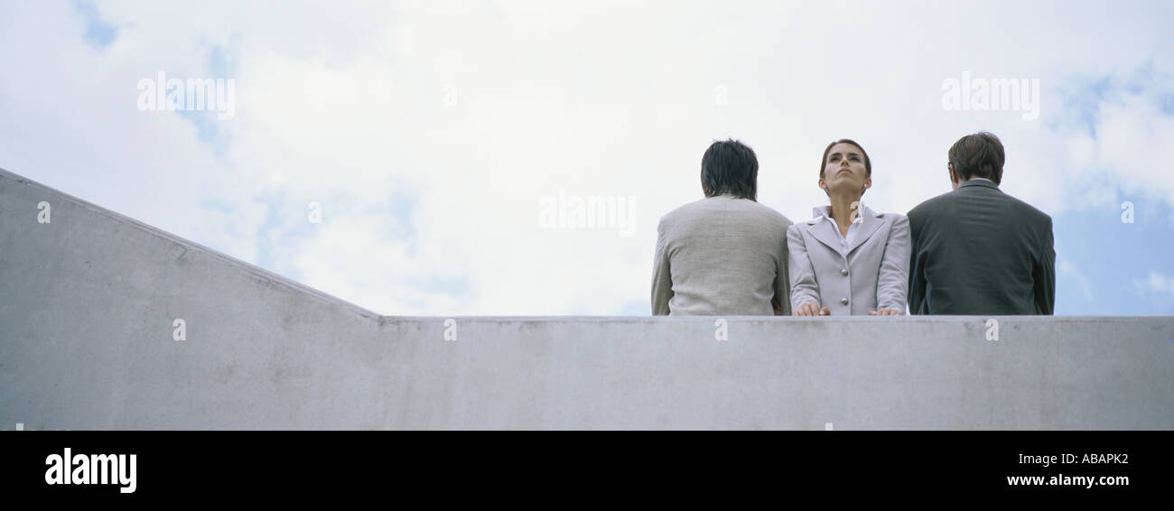 Woman standing between two men with backs turned - Stock Image
