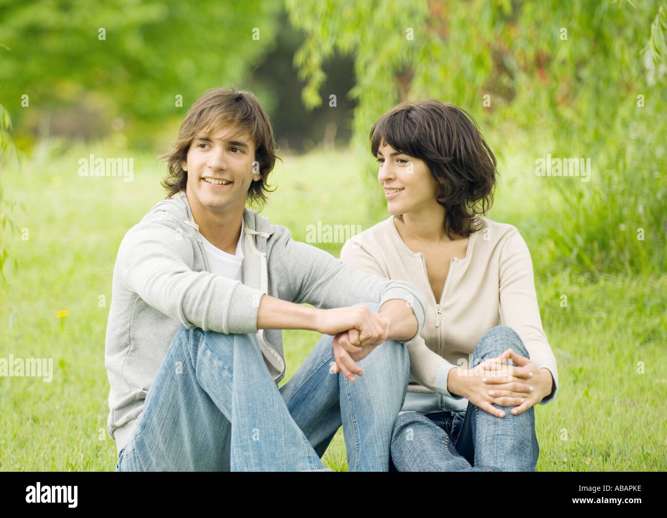 Young couple sitting on grass - Stock Image