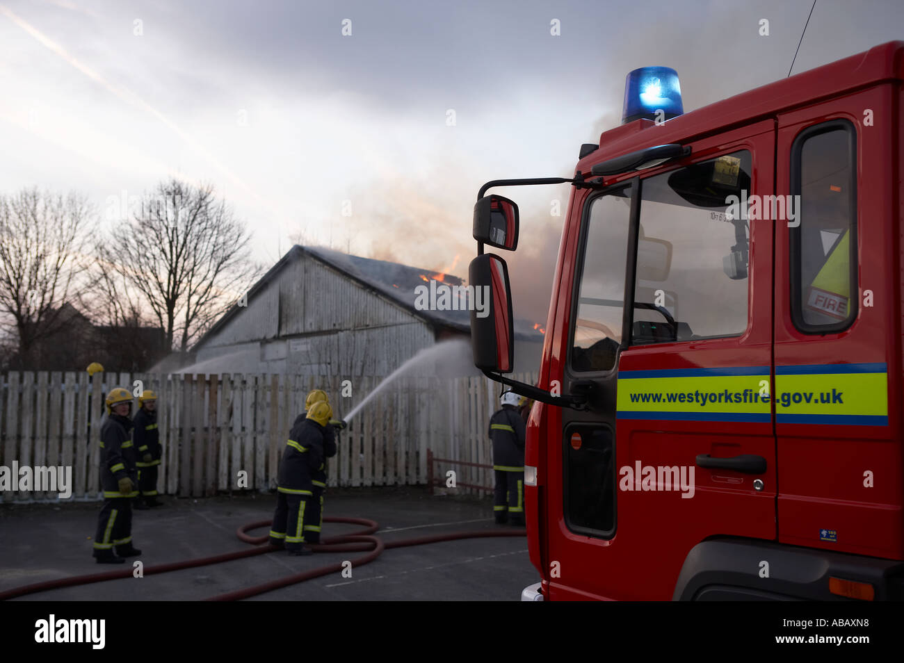 FIRE SERVICE ATTACKING BURNING BUILDING - Stock Image