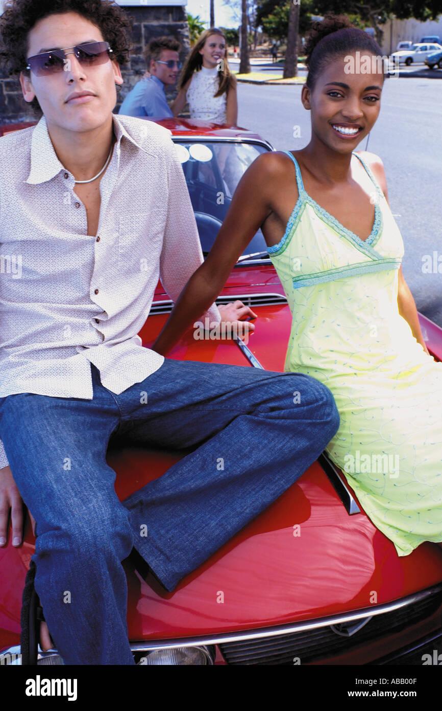 Couple sitting on car bonnet - Stock Image