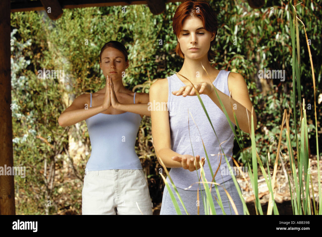 Two women practising tai chi and yoga - Stock Image