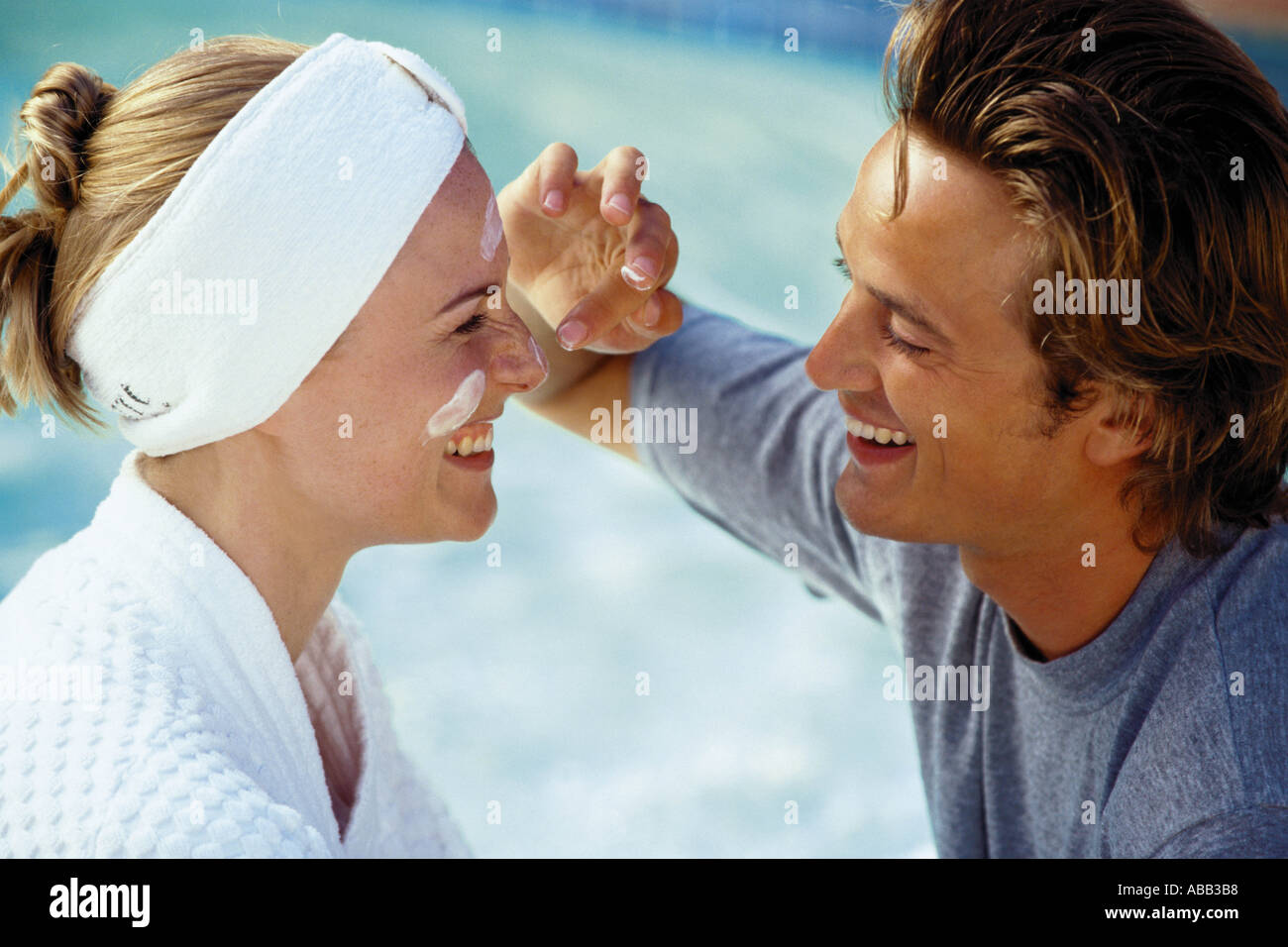 Man applying suncream to womans face - Stock Image