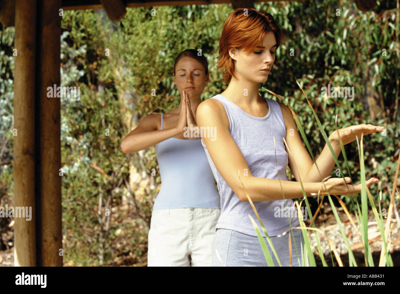 Two women practising yoga and tai chi - Stock Image