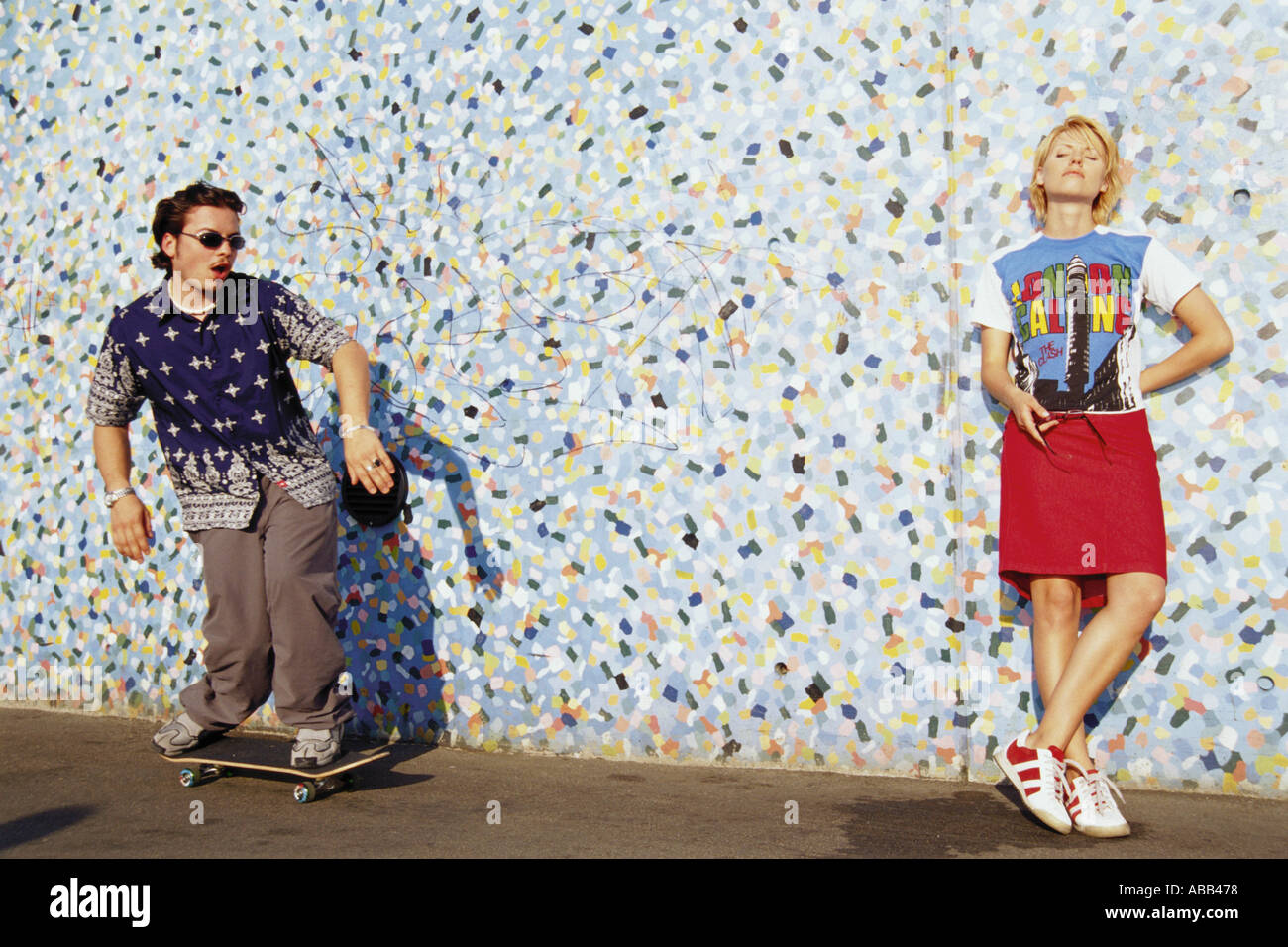 Two young adults near a patterned wall - Stock Image