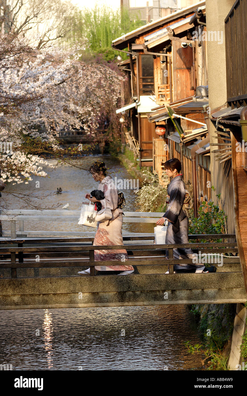 Women Dressed in Traditional Clothes cross the Shirakawa River, Gion During Cherry Blossom Season, Kyoto, Japan - Stock Image
