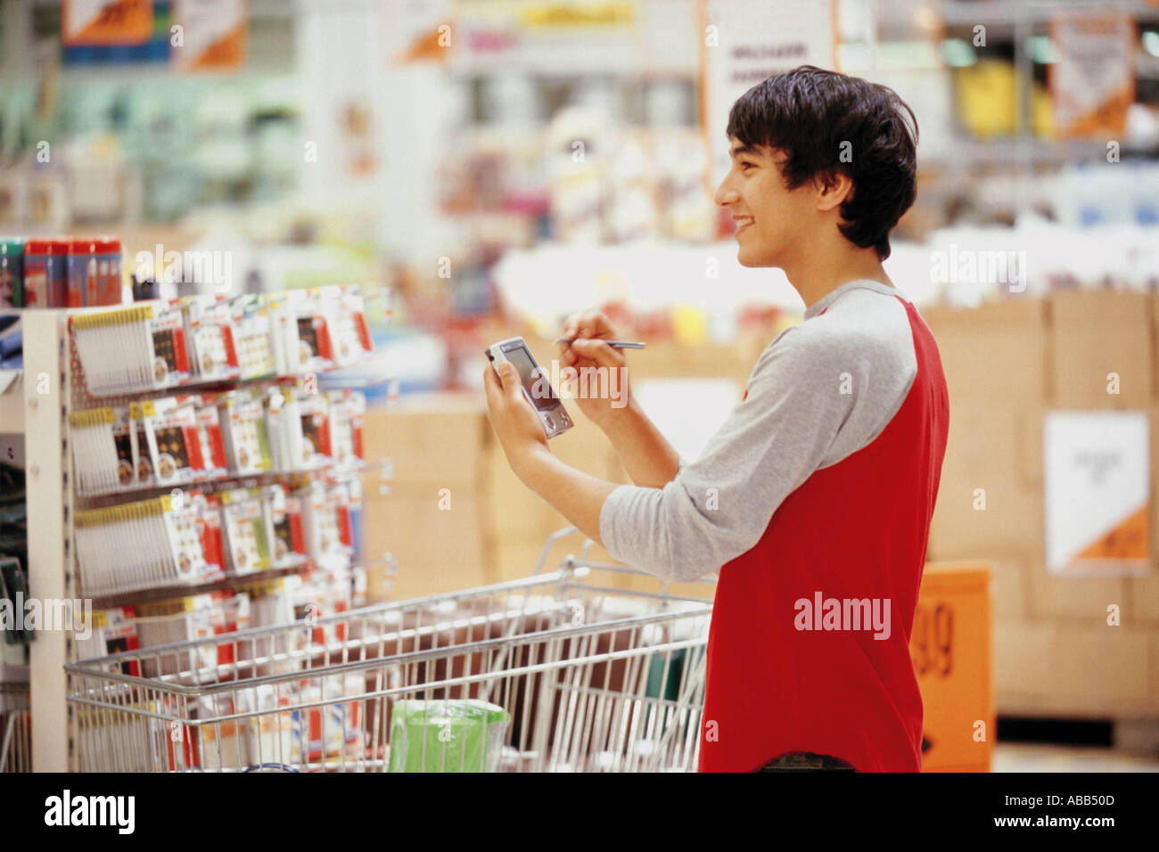 Man in using a handheld computer in shop - Stock Image