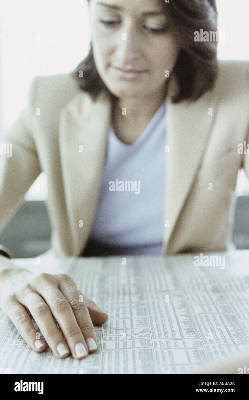 Businesswoman reading stocks and shares - Stock Image