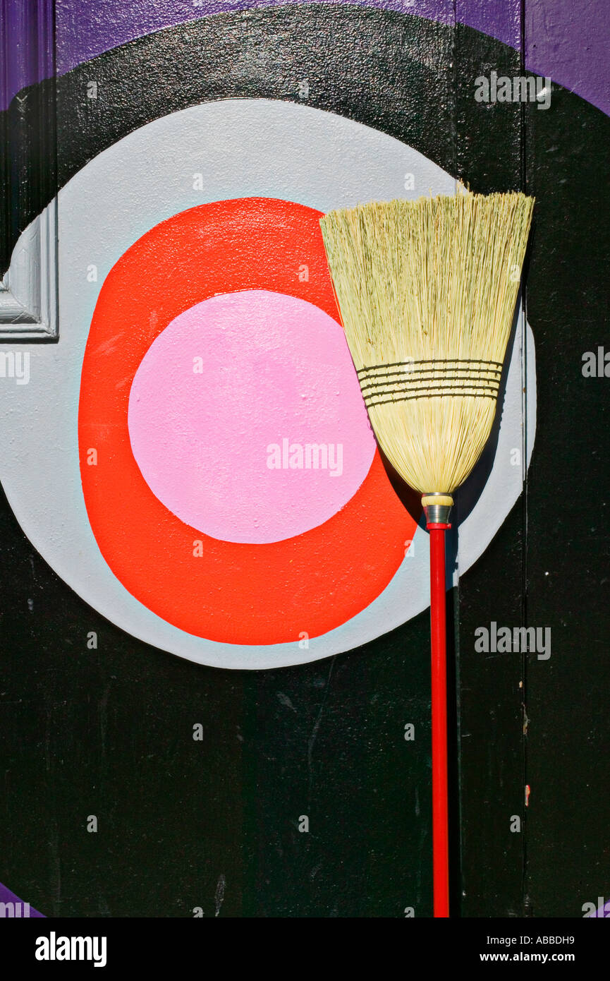 Broom against wall with pink circle at rest - Stock Image