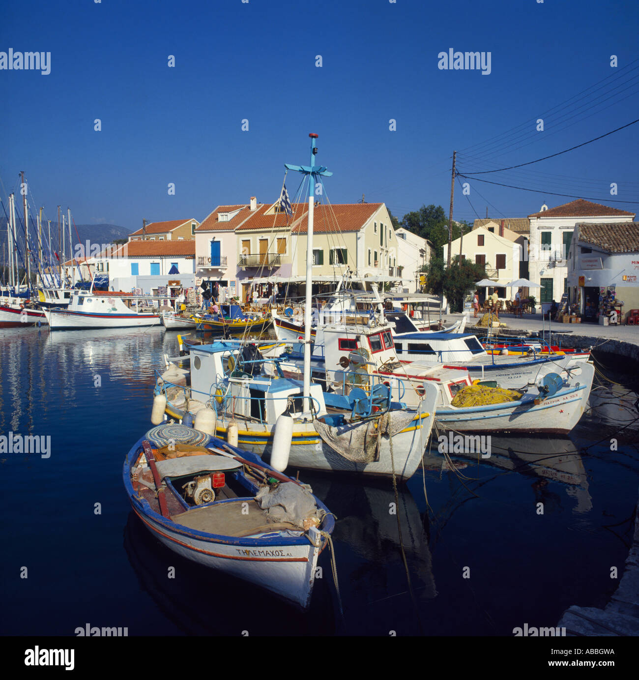 Fishing boats moored in harbour with cafes shops and houses on quayside Fiscardo Cephalonia Island Greek Islands Greece - Stock Image