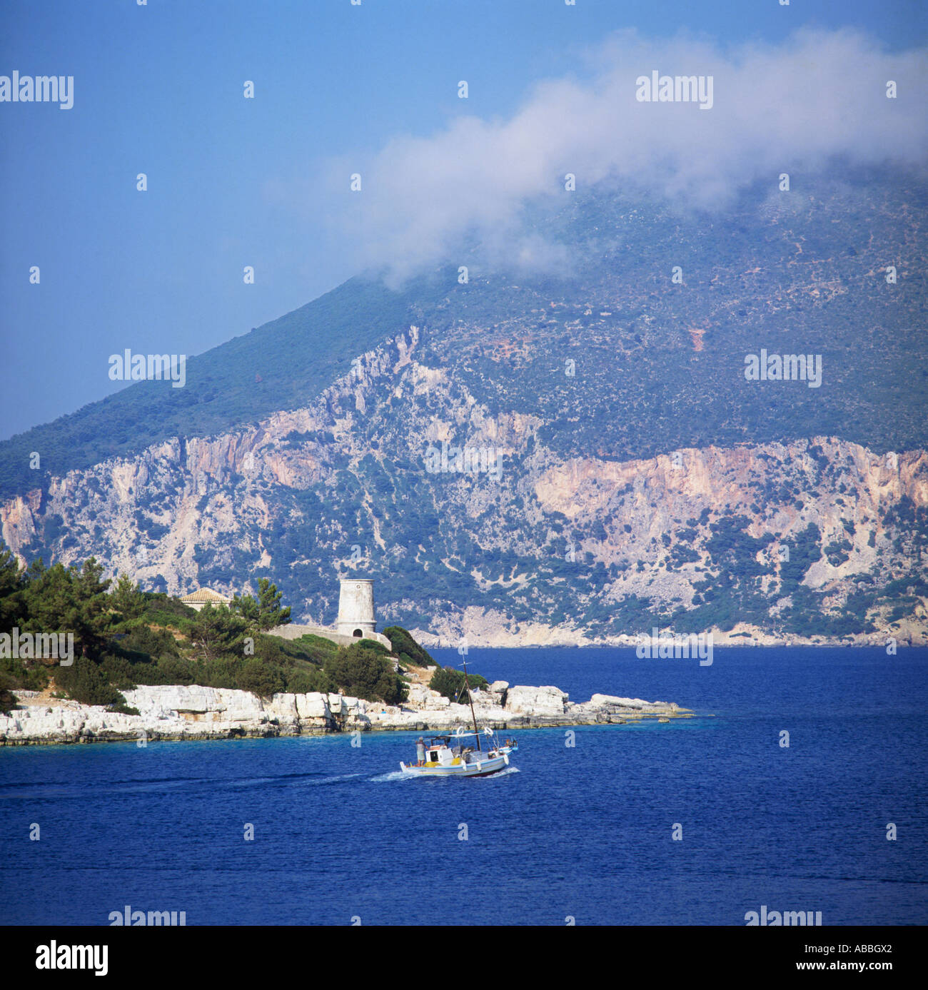 Boat travelling to harbour entrance with tower on rocks and Ithaca mountains behind Fiscardo Cephalonia Greek Islands Greece - Stock Image