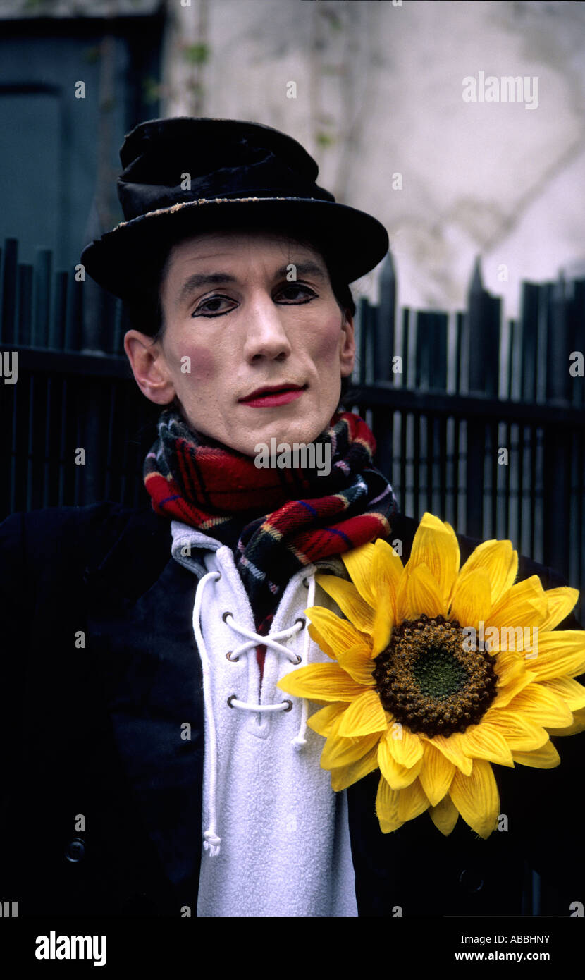 Parisian street white face mime artist with outsized yellow sunflower buttonhole - Stock Image