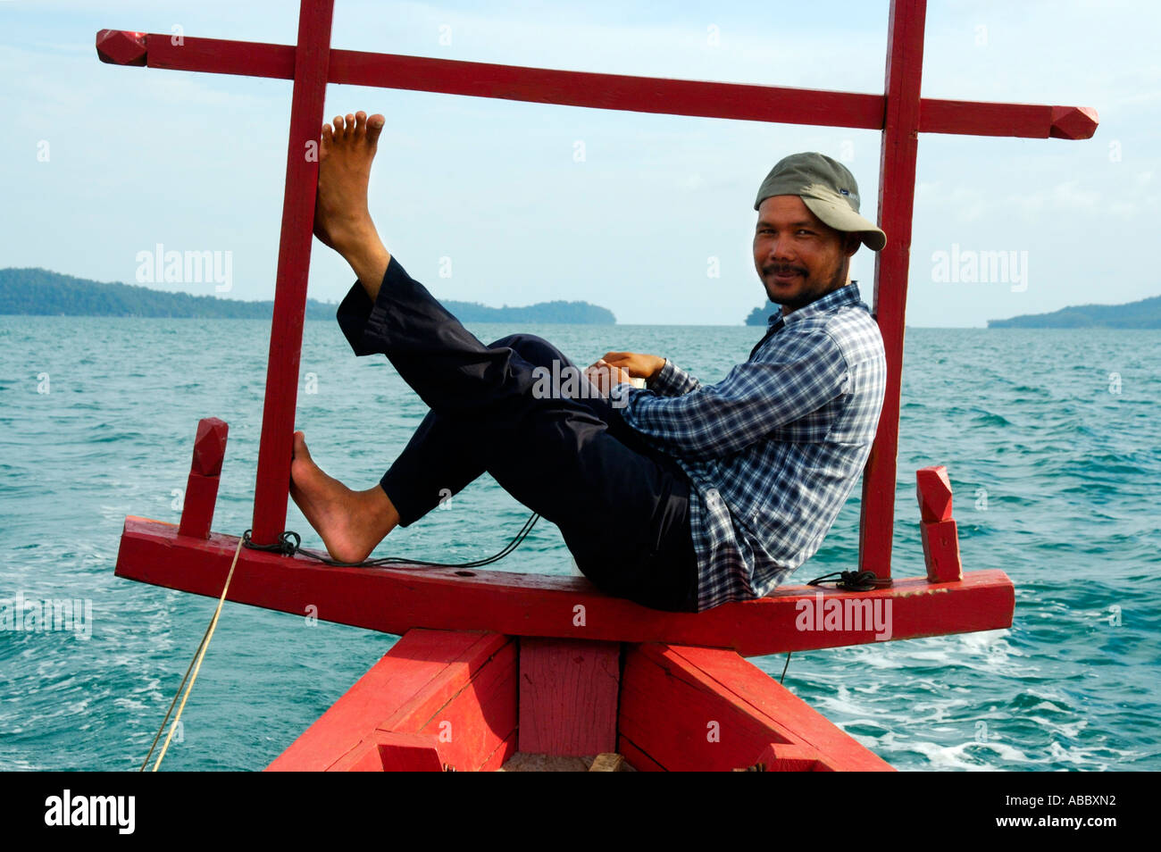 Khmer boatman captain squats in the stern of his fisher boat near Sihanoukville Kompong Som Cambodia - Stock Image
