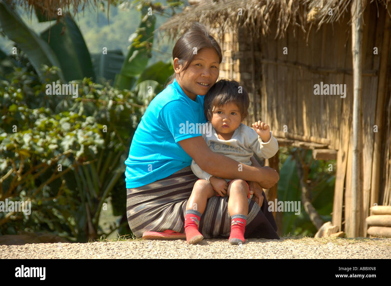 Smiling mother carries child in her arms Laos - Stock Image